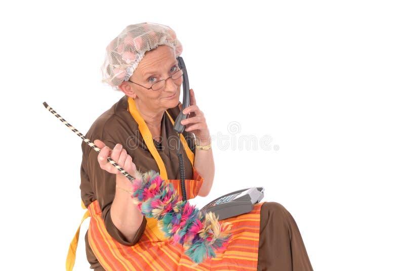 Signora di pulizia sul telefono immagini stock libere da diritti
