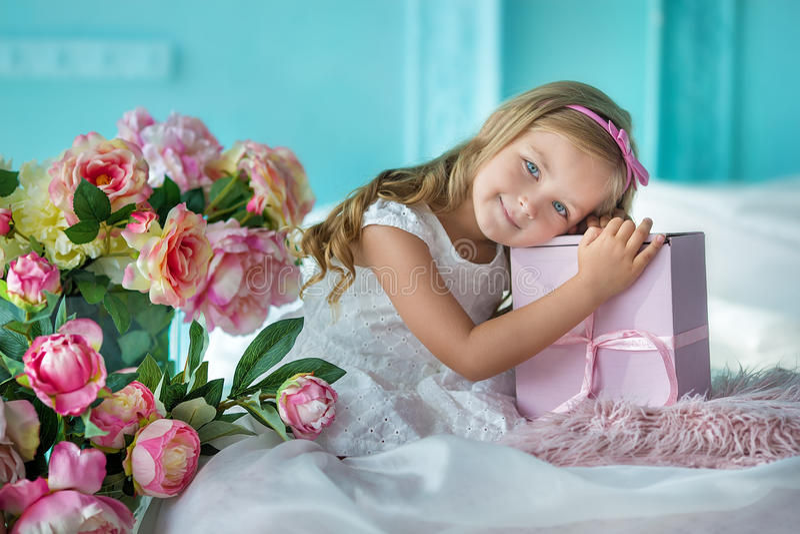 Signora di sguardo piacevole della ragazza in vestito sveglio che si siede su un sofà con i fiori in vestito alla moda bianco fotografie stock