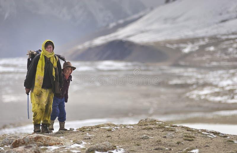 Signora di Shimshali e la sua salita del figlio nelle aree pericolose per portare a casa i yak persi fotografia stock