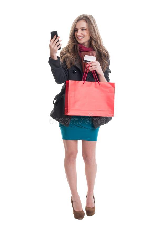 Signora di Shoping che controlla il suo smartphone immagini stock libere da diritti
