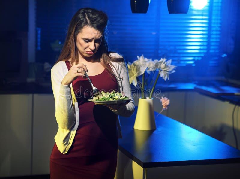 Signora dimessa che mangia un'insalata immagini stock
