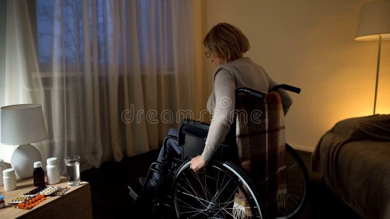 Signora disabile sola che pensa alla sua vita vicino alla finestra sulla via, solitudine immagini stock