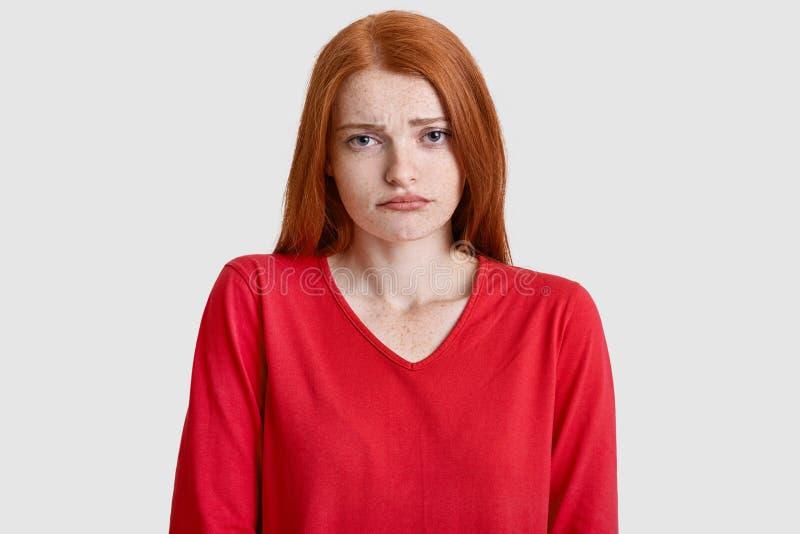 Signora dispiaciuta dello zenzero aggrotta le sopracciglia fronte, ha pelle freckled, indossa il saltatore rosso, doenst come qua fotografia stock