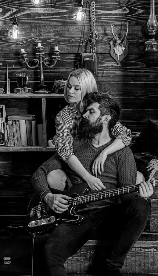 Signora ed uomo con la barba sulla chitarra vaga degli abbracci e dei giochi dei fronti Concetto romantico di sera Le coppie nell immagini stock libere da diritti