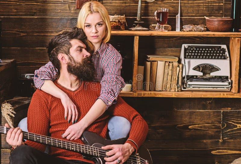 Signora ed uomo con la barba sulla chitarra vaga degli abbracci e dei giochi dei fronti Le coppie nell'interno d'annata di legno  immagini stock