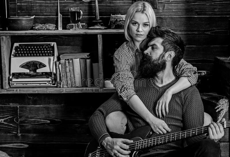 Signora ed uomo con la barba sulla chitarra vaga degli abbracci e dei giochi dei fronti Le coppie nell'interno d'annata di legno  fotografia stock libera da diritti