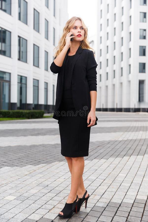 Signora elegante di affari nella conversazione integrale sul telefono fotografia stock