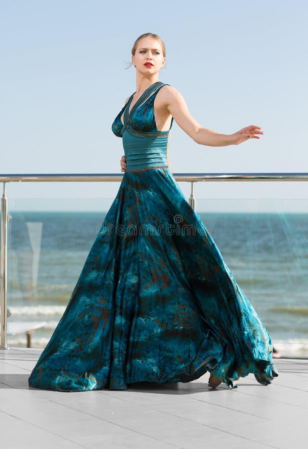 Signora elegante meravigliosa in un vestito verde smeraldo d'ondeggiamento lungo, posante vicino ad un mare blu luminoso La bella immagini stock