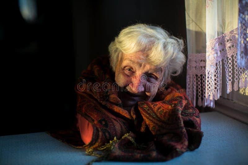 Signora felice anziana che si siede nello scuro nella casa immagini stock