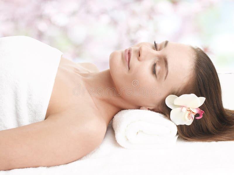 Signora felice che si rilassa nel salone di massaggio fotografia stock