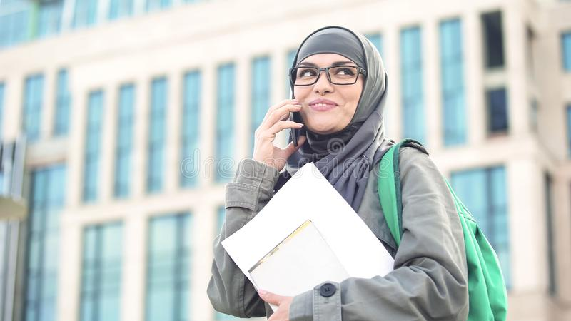 Signora felice nel hijab musulmano che parla sul telefono, tenente i documenti a disposizione, città universitaria immagine stock