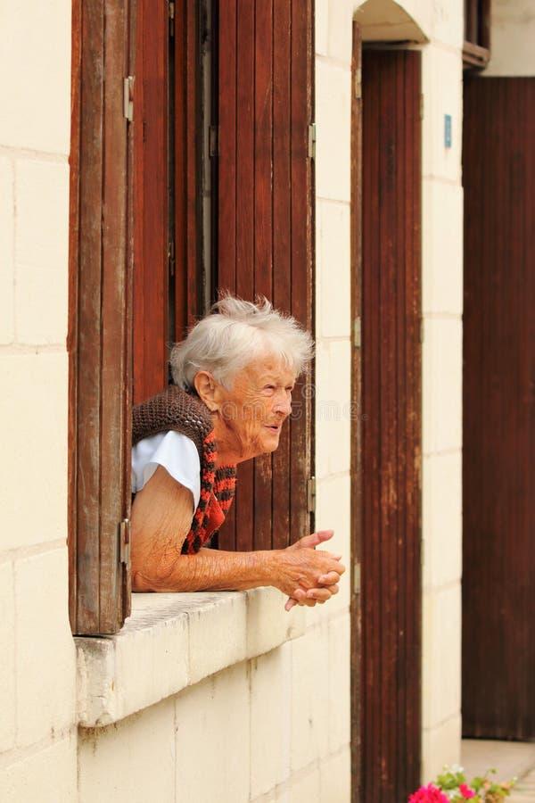 Signora francese anziana alla finestra immagine stock