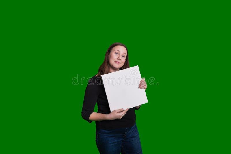 Signora giovanile graziosa che giudica un bordo bianco in bianco pronto ad aggiungere contenuto immagine stock libera da diritti