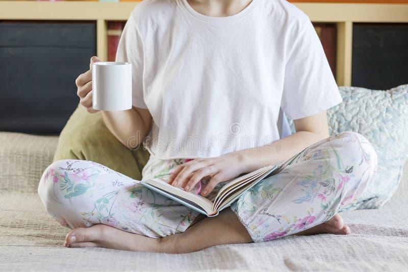 signora graziosa Bionda-dai capelli in pigiami sta bevendo il suo cof di mattina fotografie stock