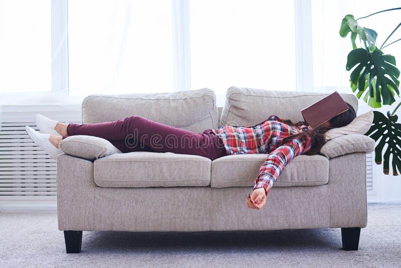 Signora graziosa che dorme mentre libro di lettura immagini stock libere da diritti
