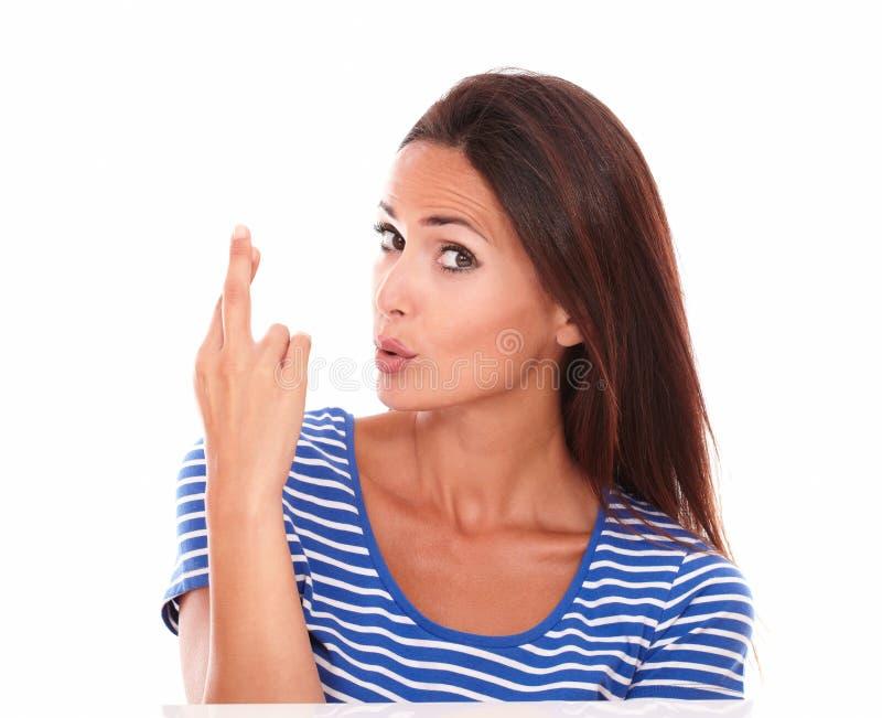 Signora graziosa in maglietta blu che fa un segno fortunato fotografia stock libera da diritti