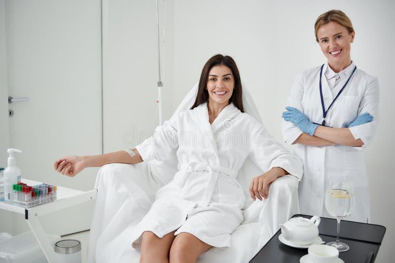 Signora incantante che riceve infusione IV mentre armi d'attraversamento di medico fotografia stock