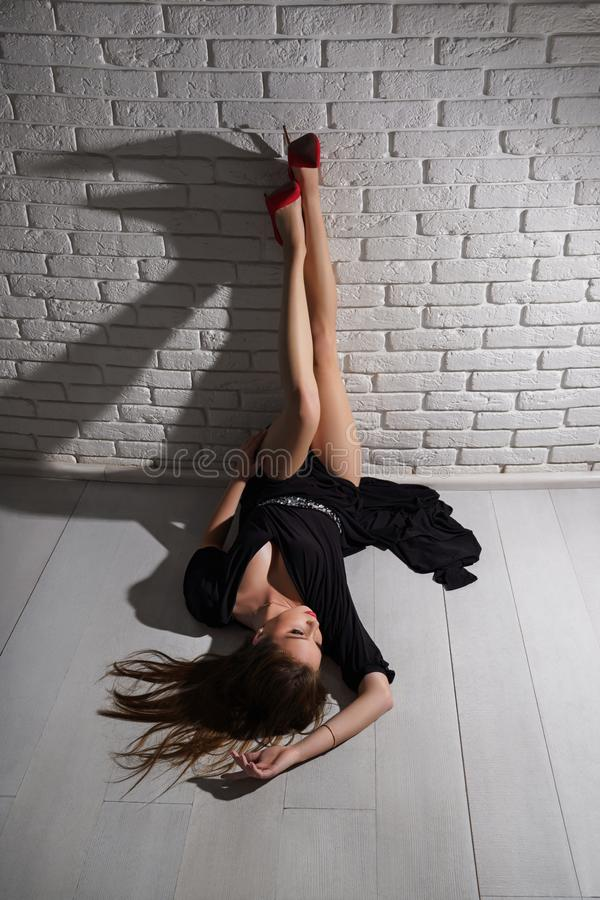 Signora incantante in vestito nero che si trova sul pavimento in studio, posante immagine stock