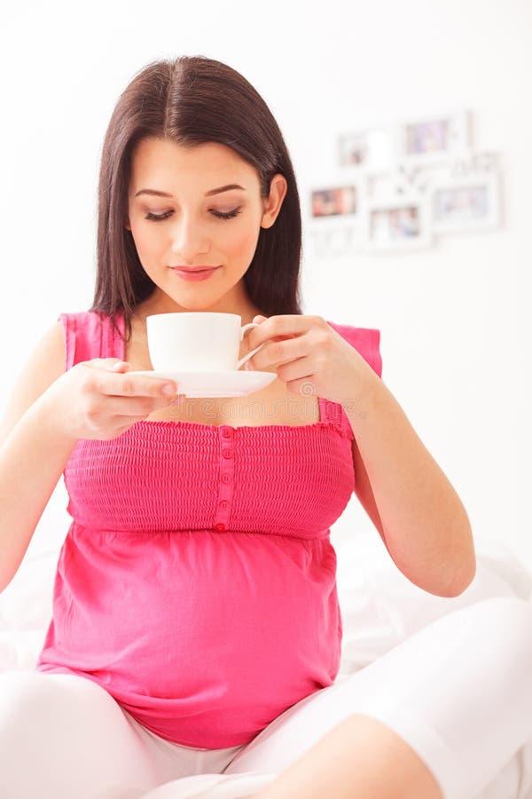 Signora incinta sveglia sta rilassandosi con la bevanda calda immagine stock