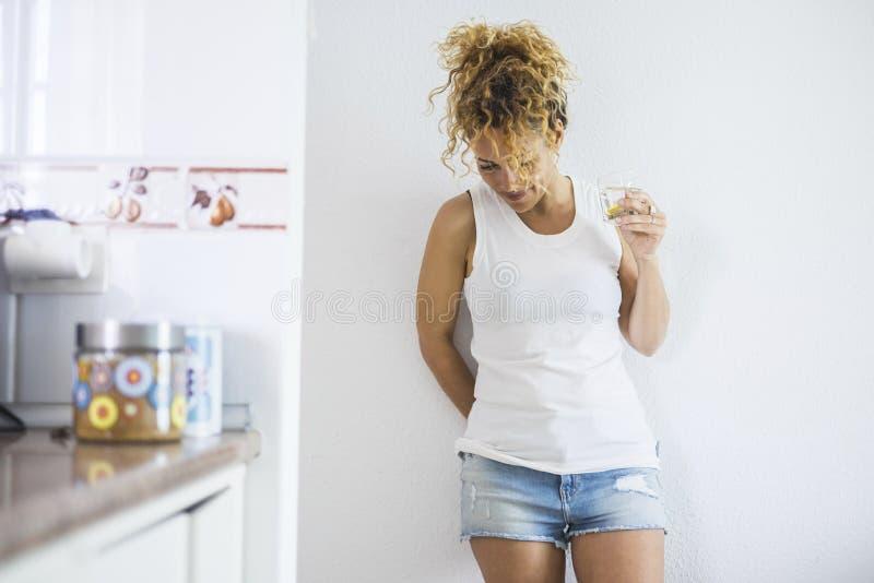 Signora indipendente sola che sta a casa vicino ad una parete e un caffè o un tè bevente della cucina nell'attività di svago dell fotografia stock