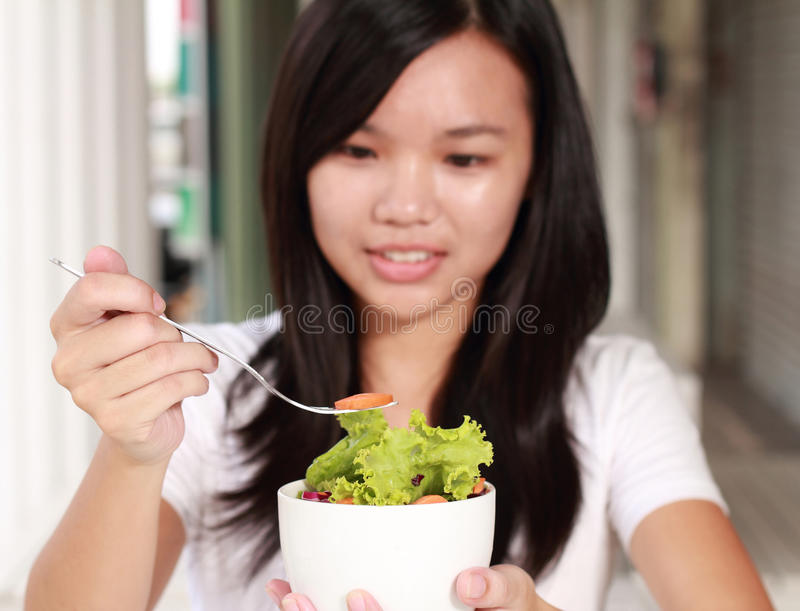 Signora mangia l'insalata di verdure sul ristorante immagine stock libera da diritti