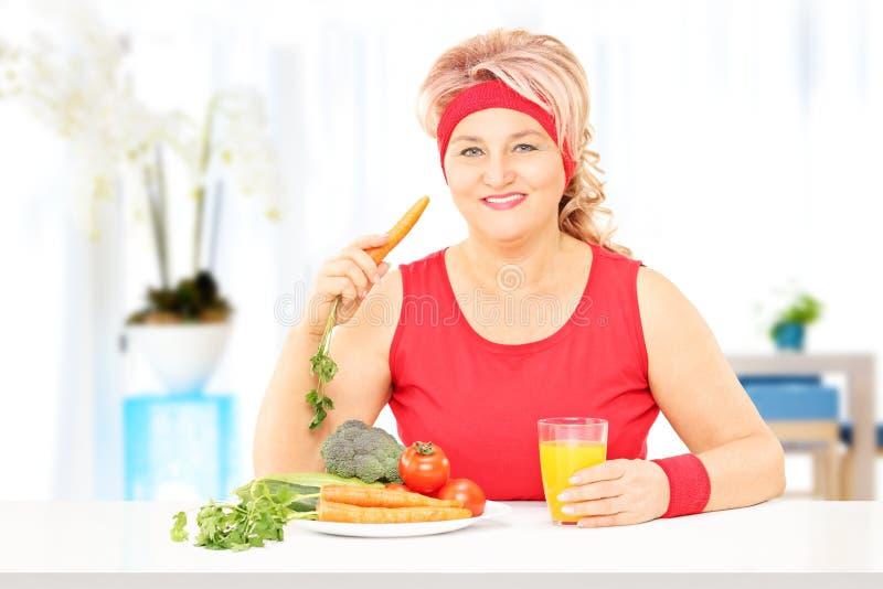 Signora matura a casa che mangia un pasto sano immagini stock