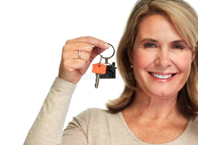 Signora matura con una chiave della casa fotografia stock