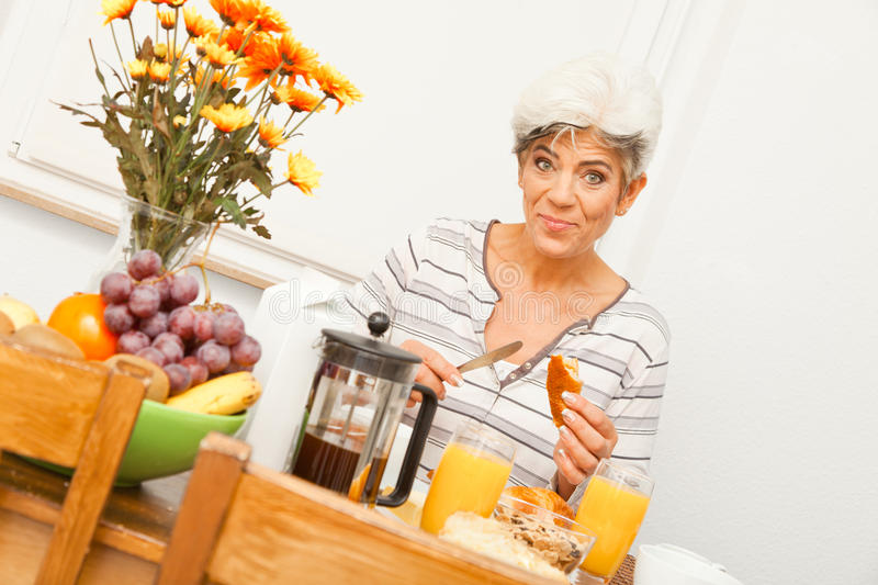 Signora matura felice Having Breakfast fotografia stock