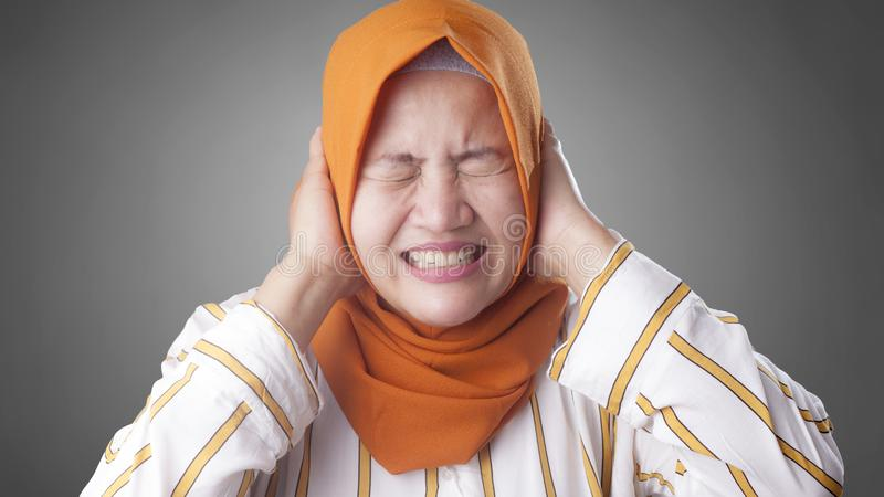 Signora musulmana asiatica Close Her Ears fotografia stock