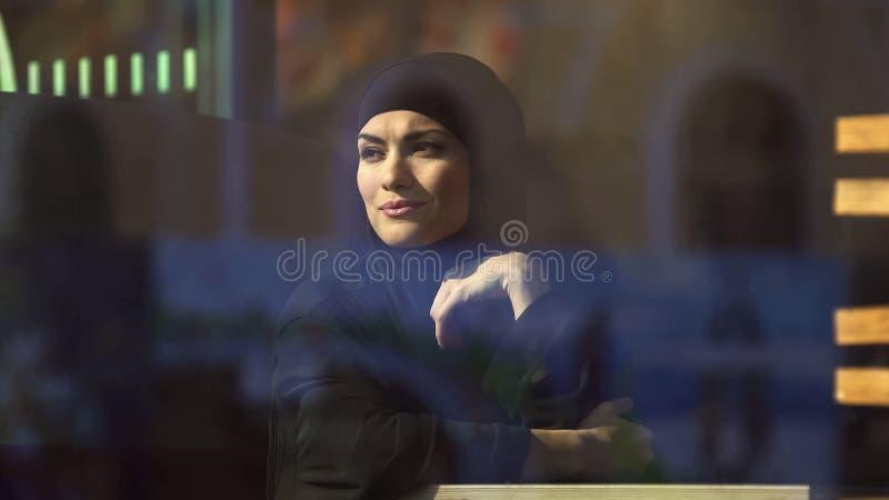 Signora musulmana attraente nel hijab che si siede in caffè, guardando nella finestra, sognante immagini stock libere da diritti