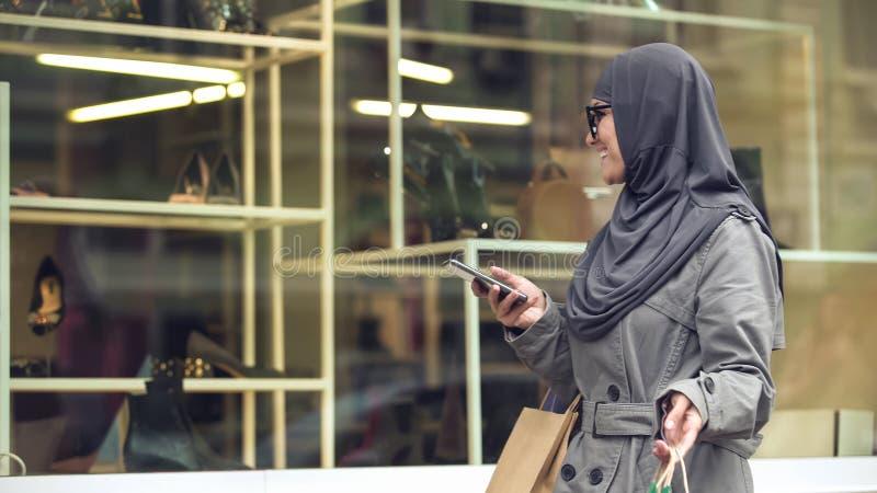 Signora musulmana felice che esamina le scarpe di modo attraverso la finestra del boutique, acquisto immagini stock libere da diritti