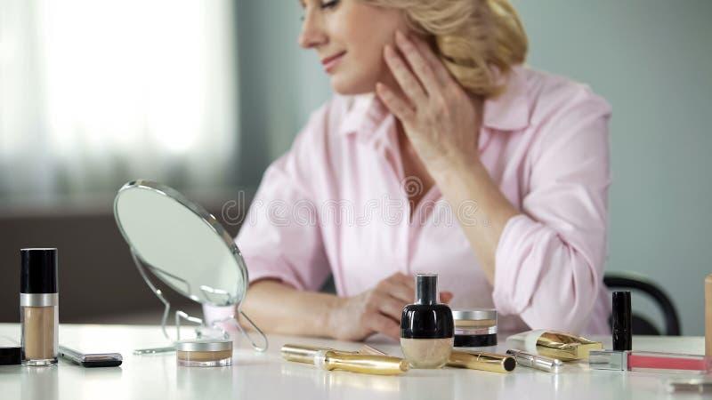 Signora nei suoi 50 soddisfatti con la condizione della pelle dopo avere usando i cosmetici antinvecchiamento fotografia stock libera da diritti