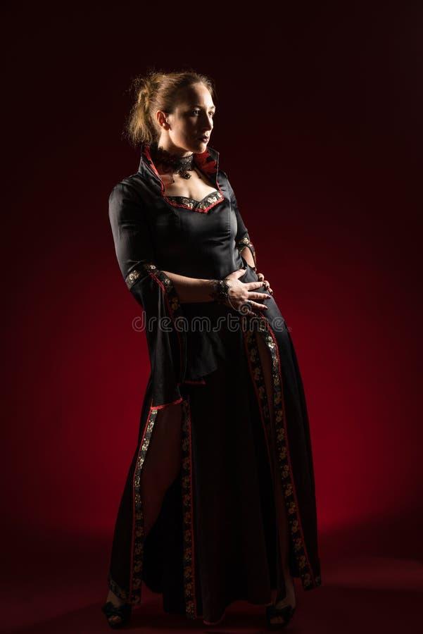 Signora nella condizione nera dell'abito e posare nello studio Ritratto di bella donna elegante in vestito da sera immagini stock