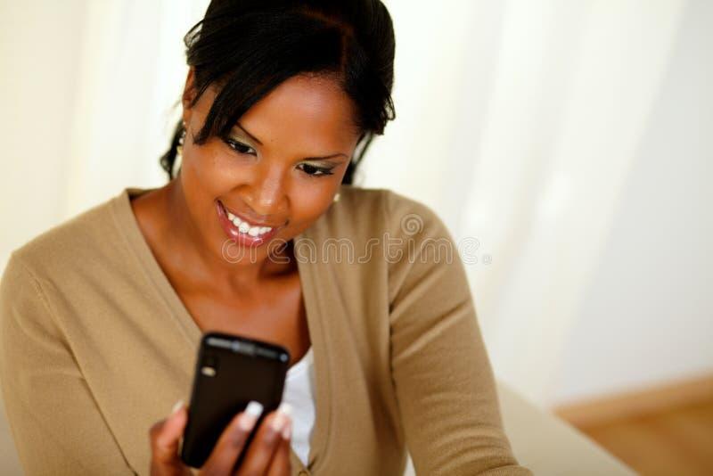 Signora nera Charming che trasmette un messaggio dal cellulare fotografia stock