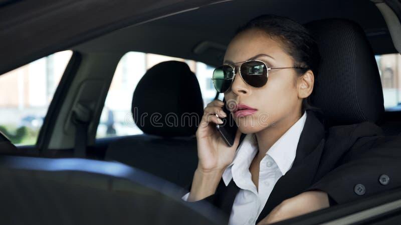 Signora in occhiali da sole che si siedono in automobile e che parlano sul cellulare, agente di polizia in servizio immagine stock