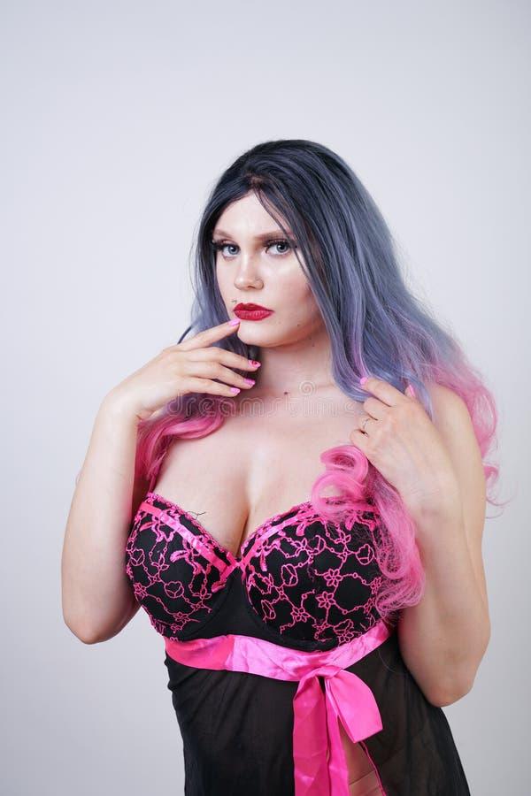 Signora paffuta graziosa sveglia che porta il vestito sessuale dalla biancheria della bamboletta sul fondo bianco dello studio immagini stock