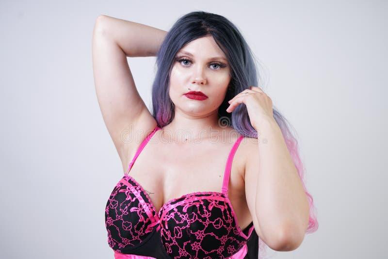 Signora paffuta graziosa sveglia che porta il vestito sessuale dalla biancheria della bamboletta sul fondo bianco dello studio immagine stock libera da diritti