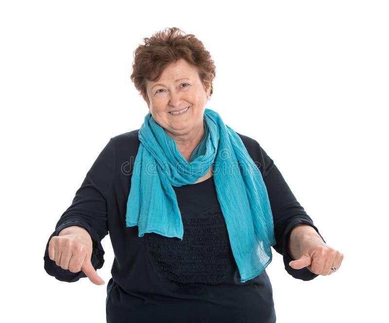 Signora più anziana isolata divertente in blu che fa i pollici giù gesture immagini stock libere da diritti