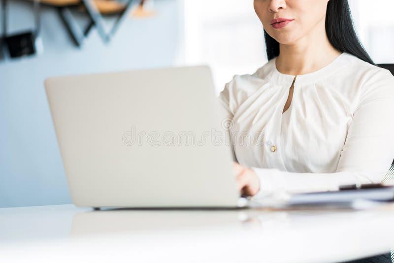Signora piacevole concentrata di affari che lavora nell'ufficio immagini stock