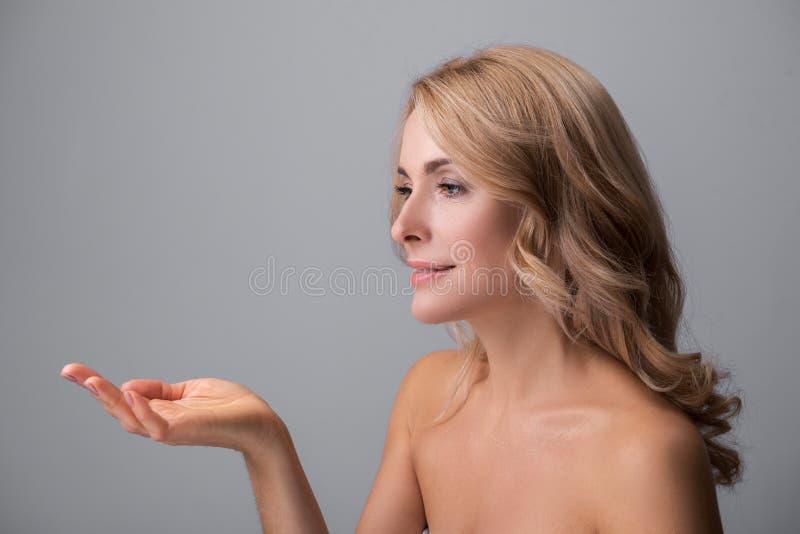 Signora piacevole sta mostrando qualcosa sulla sua mano fotografia stock libera da diritti