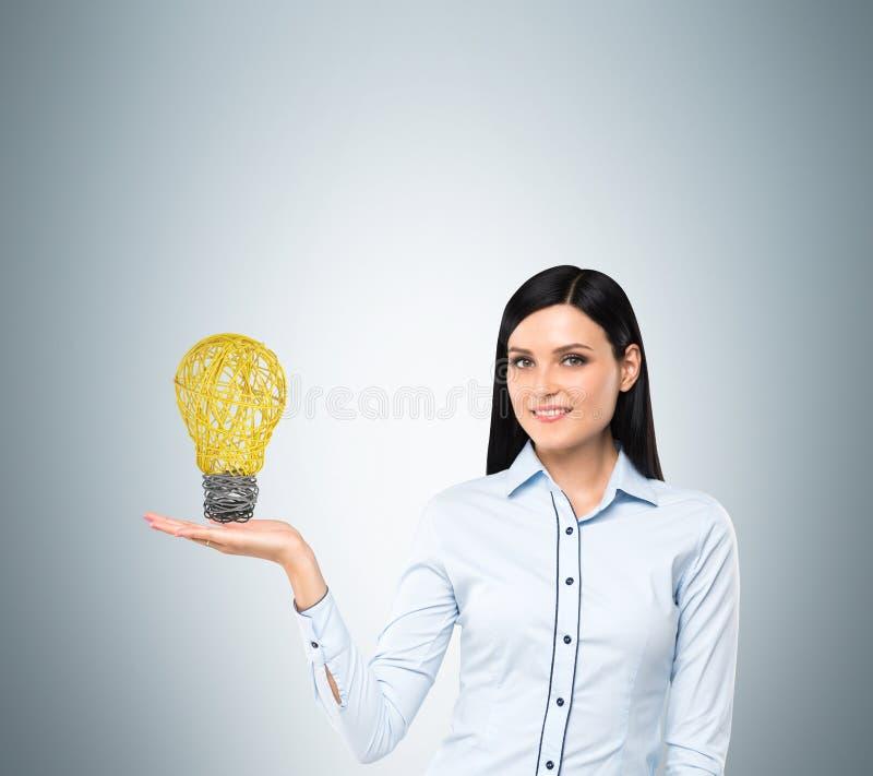 Signora presenta una lampadina come concetto di nuova idea nell'affare fotografie stock libere da diritti