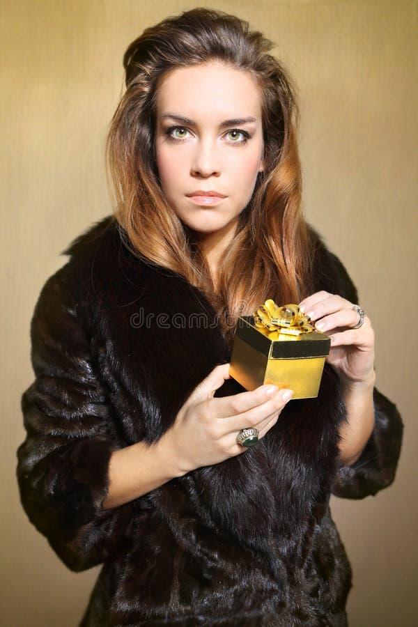 Signora ricca in una pelliccia insoddisfatta con il presente fotografia stock