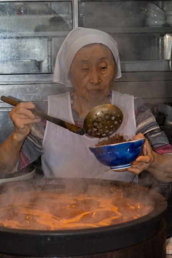 Signora scava la zuppa di pesce sul mercato ittico di Tsukiji di Tokyo immagini stock libere da diritti
