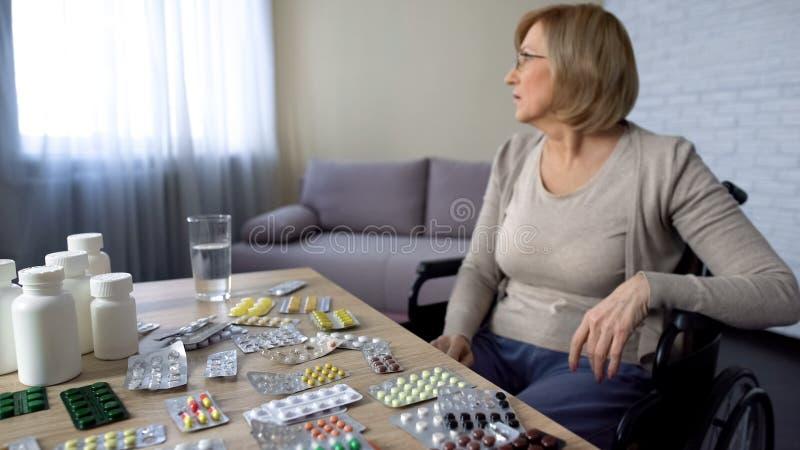 Signora in sedia a rotelle che prende trattamento di lesione della medicina dell'analgesico, casa di cura immagine stock