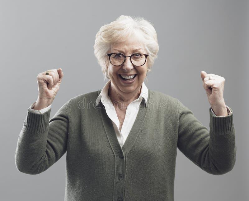 Signora senior allegra che celebra la sua vittoria con i pugni alzati fotografie stock libere da diritti
