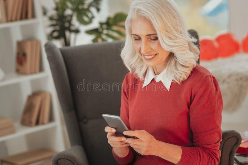 Signora senior allegra che passa in rassegna i siti divertenti sullo smartphone fotografia stock libera da diritti