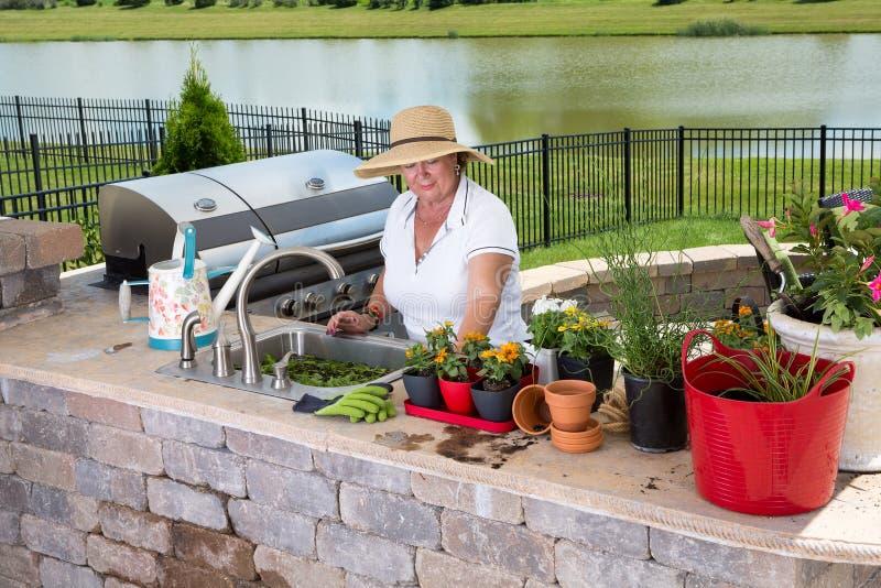 Signora senior che lavora nella sua cucina di estate fotografia stock libera da diritti