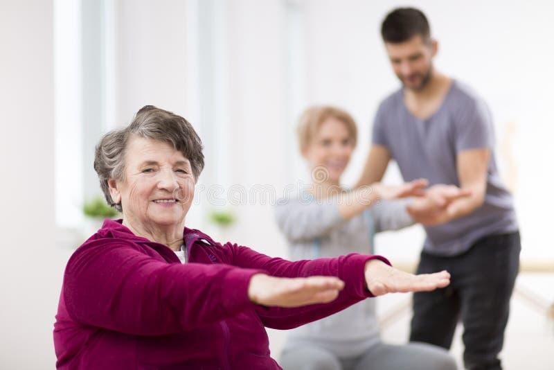 Signora senior che si esercita durante la fisioterapia del gruppo al centro di riabilitazione fotografia stock libera da diritti
