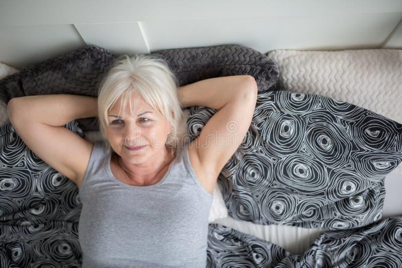 Signora senior che si trova a letto sognando fotografie stock libere da diritti