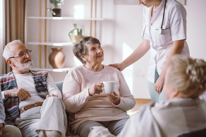 Signora senior con l'infermiere e sedersi con i suoi amici anziani fotografia stock